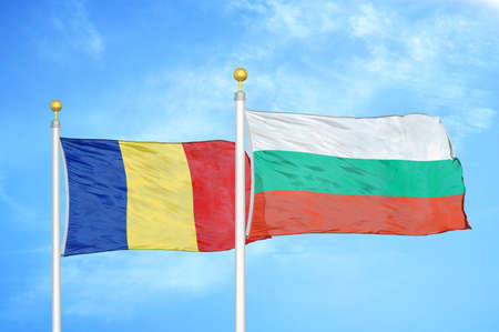 Romania and Bulgaria two flags on flagpoles and blue cloudy sky background