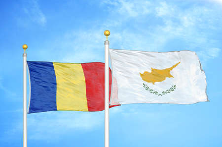 Romania and Cyprus two flags on flagpoles and blue cloudy sky background