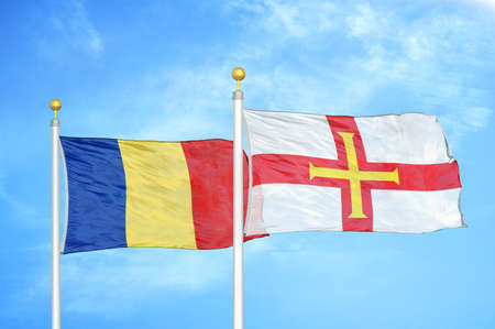 Romania and Guernsey two flags on flagpoles and blue cloudy sky background