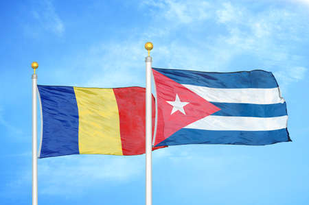 Romania and Cuba two flags on flagpoles and blue cloudy sky background