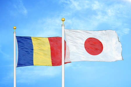 Romania and Japan two flags on flagpoles and blue cloudy sky background Stock Photo