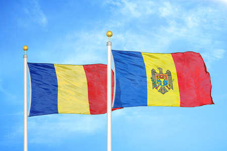 Romania and Moldova two flags on flagpoles and blue cloudy sky background