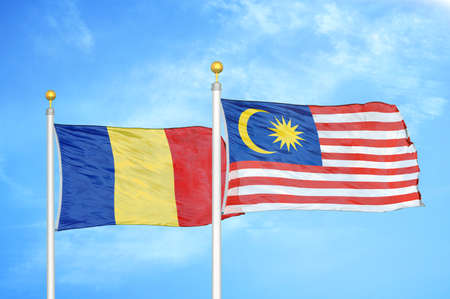 Romania and Malaysia two flags on flagpoles and blue cloudy sky background