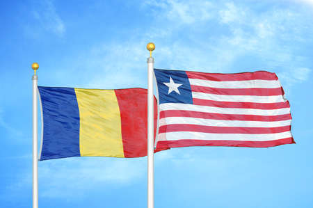 Romania and Liberia two flags on flagpoles and blue cloudy sky background