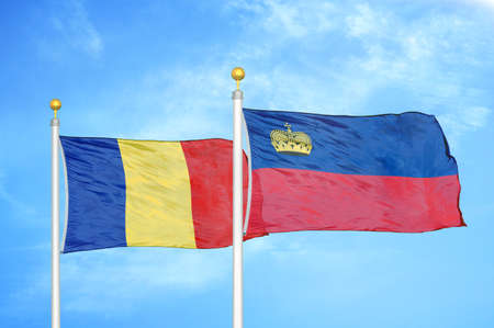 Romania and Liechtenstein two flags on flagpoles and blue cloudy sky background