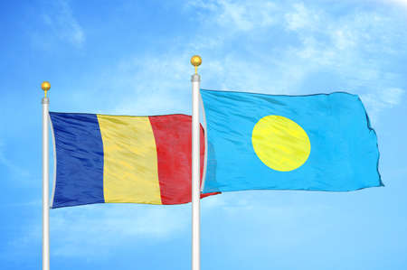 Romania and Palau two flags on flagpoles and blue cloudy sky background Stock Photo