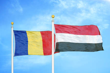 Romania and Yemen two flags on flagpoles and blue cloudy sky background Stock Photo