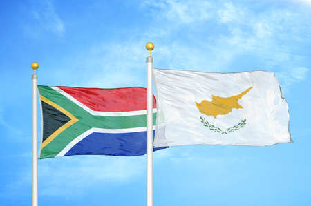 South Africa and Cyprus two flags on flagpoles and blue cloudy sky background