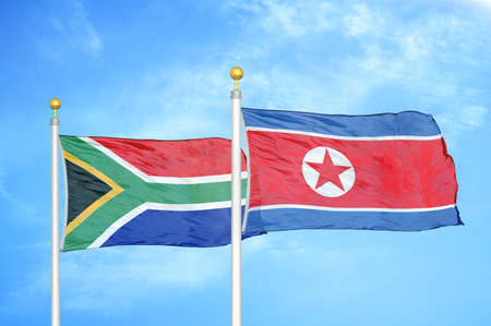 South Africa and North Korea two flags on flagpoles and blue cloudy sky background