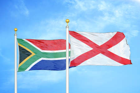South Africa and Northern Ireland two flags on flagpoles and blue cloudy sky background