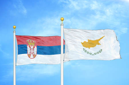 Serbia and Cyprus two flags on flagpoles and blue cloudy sky background