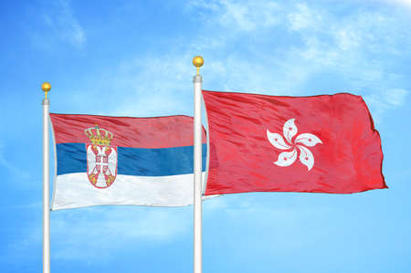 Serbia and Hong Kong two flags on flagpoles and blue cloudy sky background