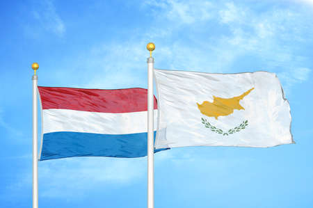 Netherlands and Cyprus two flags on flagpoles and blue cloudy sky background