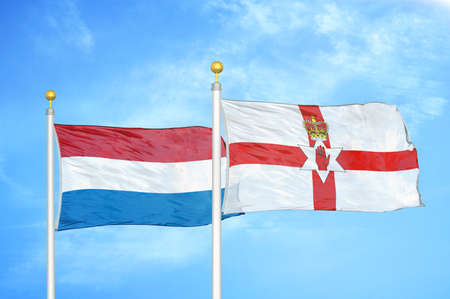 Netherlands and Northern Ireland two flags on flagpoles and blue cloudy sky background