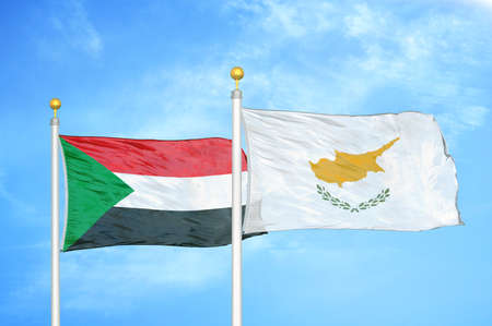Sudan and Cyprus two flags on flagpoles and blue cloudy sky background Imagens