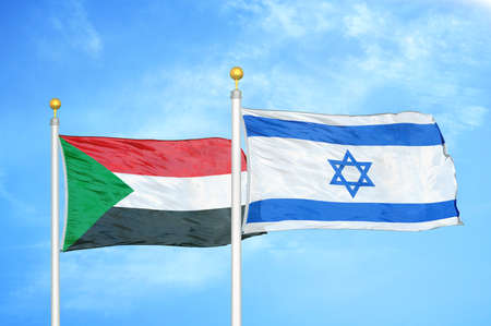 Sudan and Israel two flags on flagpoles and blue cloudy sky background
