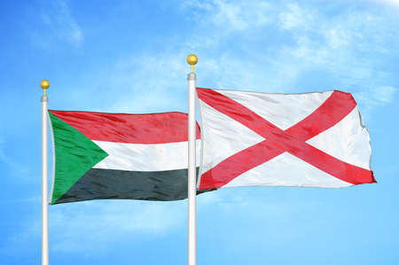 Sudan and Northern Ireland two flags on flagpoles and blue cloudy sky background Stock Photo