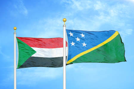 Sudan and Solomon Islands two flags on flagpoles and blue cloudy sky background