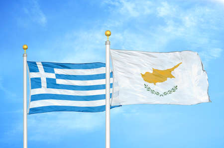 Greece and Cyprus two flags on flagpoles and blue cloudy sky background