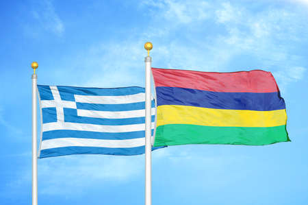 Greece and Mauritius two flags on flagpoles and blue cloudy sky background Фото со стока