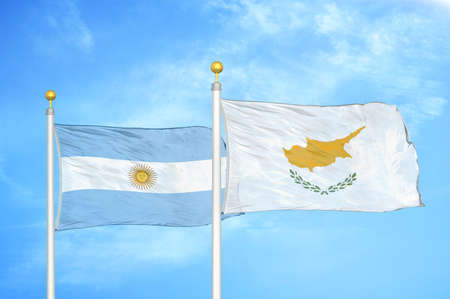 Argentina and Cyprus two flags on flagpoles and blue cloudy sky background