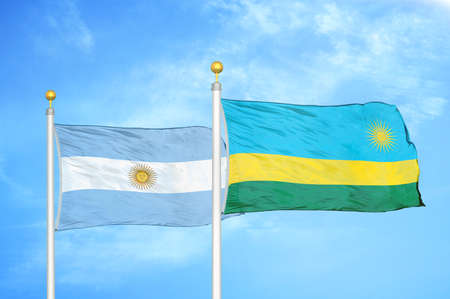 Argentina and Rwanda two flags on flagpoles and blue cloudy sky background Archivio Fotografico
