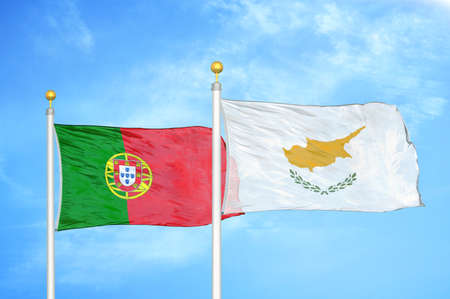 Portugal and Cyprus two flags on flagpoles and blue cloudy sky background Imagens