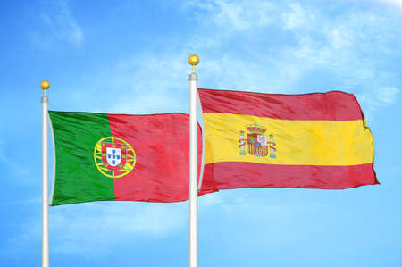 Portugal and Spain two flags on flagpoles and blue cloudy sky background