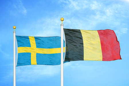 Sweden and Belgium two flags on flagpoles and blue cloudy sky background
