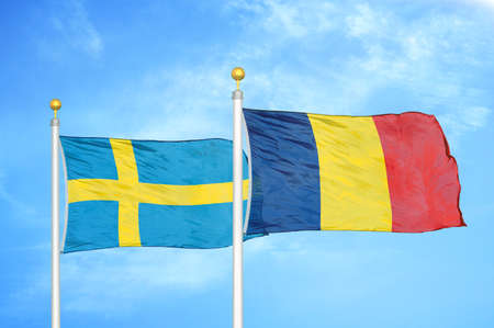 Sweden and Chad two flags on flagpoles and blue cloudy sky background