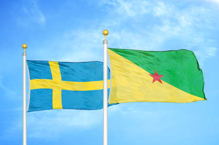 Sweden and French Guiana two flags on flagpoles and blue cloudy sky background