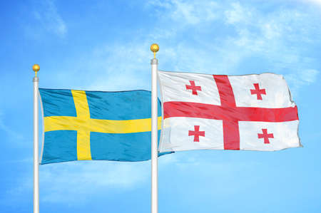 Sweden and Georgia two flags on flagpoles and blue cloudy sky background Standard-Bild