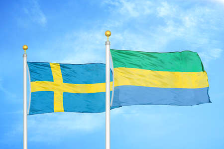 Sweden and Gabon two flags on flagpoles and blue cloudy sky background