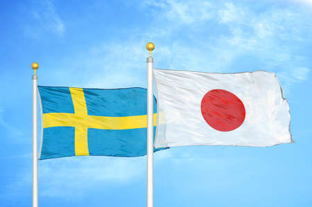 Sweden and Japan two flags on flagpoles and blue cloudy sky background Standard-Bild