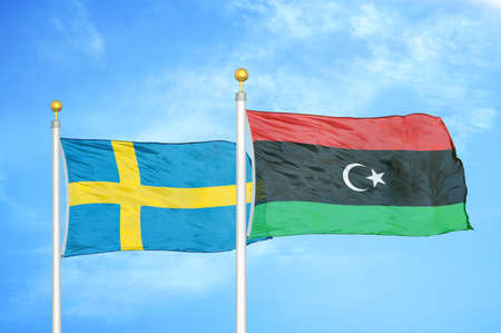 Sweden and Libya two flags on flagpoles and blue cloudy sky background