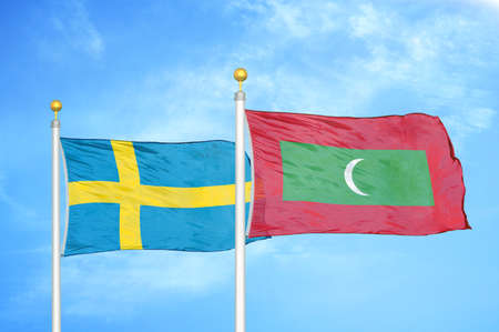 Sweden and Maldives two flags on flagpoles and blue cloudy sky background
