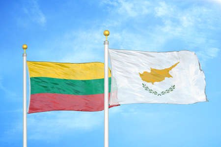 Lithuania and Cyprus two flags on flagpoles and blue cloudy sky background