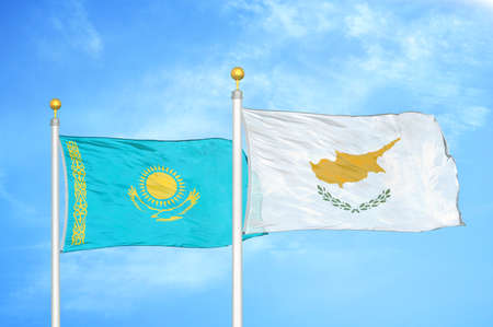 Kazakhstan and Cyprus two flags on flagpoles and blue cloudy sky background