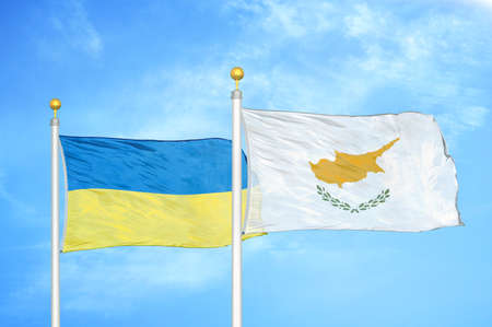 Ukraine and Cyprus two flags on flagpoles and blue cloudy sky background