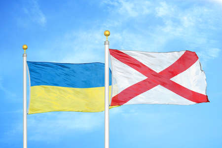 Ukraine and Northern Ireland two flags on flagpoles and blue cloudy sky background