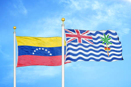 Venezuela and British Indian Territory two flags on flagpoles and blue cloudy sky background