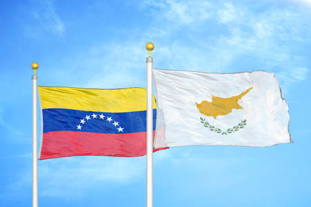 Venezuela and Cyprus two flags on flagpoles and blue cloudy sky background