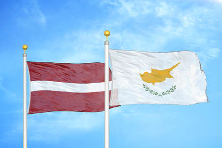 Latvia and Cyprus two flags on flagpoles and blue cloudy sky background