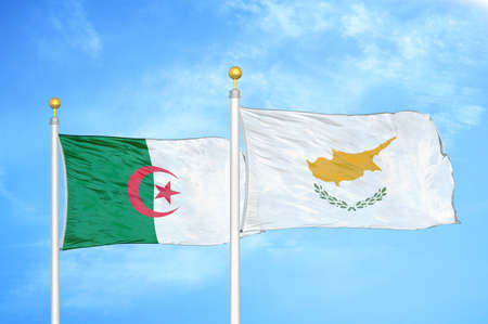 Algeria and Cyprus two flags on flagpoles and blue cloudy sky background