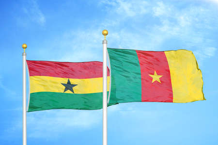 Ghana and Cameroon two flags on flagpoles and blue cloudy sky background