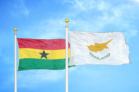 Ghana and Cyprus two flags on flagpoles and blue cloudy sky background