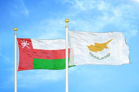 Oman and Cyprus two flags on flagpoles and blue cloudy sky background