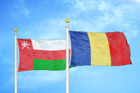 Oman and Romania two flags on flagpoles and blue cloudy sky background Stock Photo