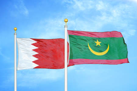 Bahrain and Mauritania two flags on flagpoles and blue cloudy sky background Фото со стока