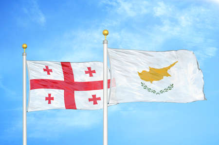 Georgia and Cyprus two flags on flagpoles and blue cloudy sky background
